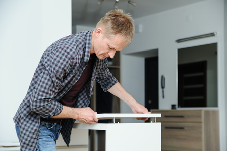 The man assembles the furniture at home. He sets the top of the chest of drawers.