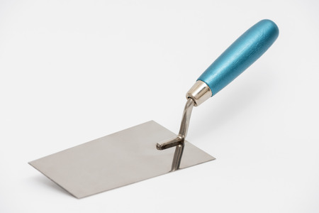 Construction trowel on a white background. Stainless steel trowel with a blue wooden handle.