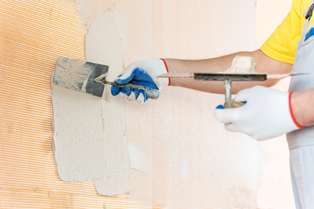 A worker is applying putty on a glass mesh on the wall. He is using a trowel.