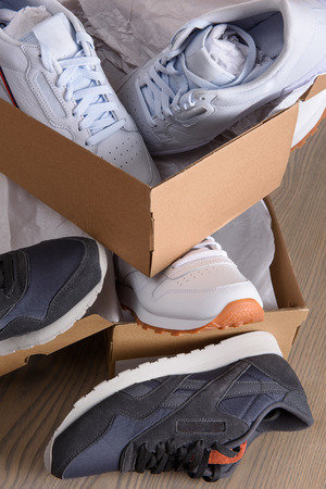 Sneakers in cardboard boxes on a wooden board.