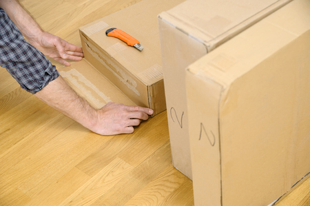 A man is unpacking the cardboard boxes. It is opening the side of the package.