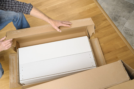 A man is unpacking a cardboard box with furniture. On the floor there is a box with white boards.