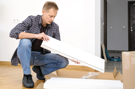 The man is holding a furniture board. On the floor there is a box with white boards.