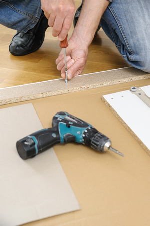 A man is assembling the furniture at home. He is installing Joint Connector Bolts in the furniture board. Фото со стока