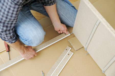 A man is assembling the furniture at home. He is mounting and fastening the frame of the chest of drawers.