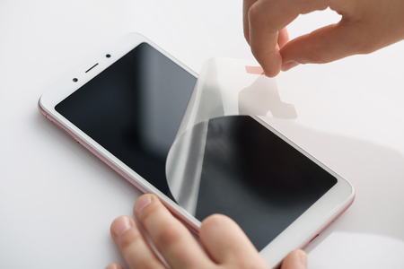 The girls hands are removing the protective film from the screen of the smartphone. Фото со стока