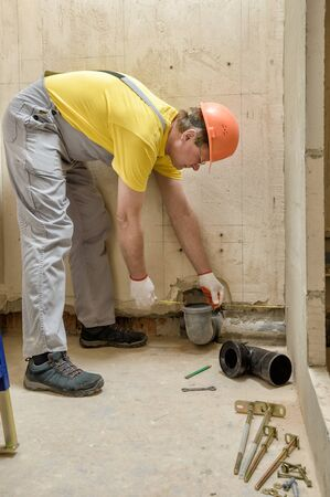 The worker is installing a sewage drain pipe to install the built-in tank of the toilet.