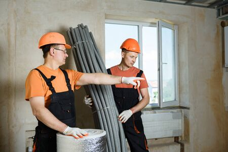 Workers with thermal insulation for the floor and pipes of the home heating system.