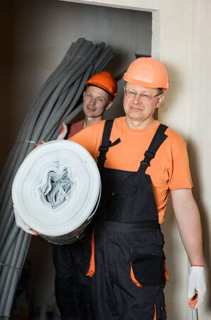 Workers are carrying thermal insulation for the floor and pipes of the home heating system. Stok Fotoğraf - 129600492