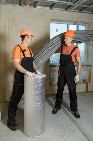 Workers are carrying thermal insulation for the floor and pipes of the home heating system.