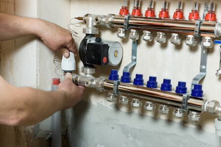 A worker is installing a thermal head on the home heating system distributor. 스톡 콘텐츠