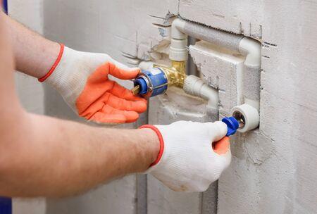 Le travailleur installe un bouchon sur le tuyau du robinet intégré. Banque d'images