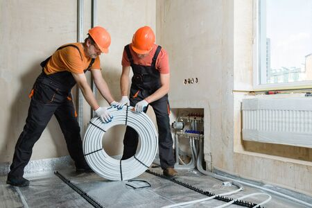 Workers are installing a pipe for the warm floor in the apartment. They are unpacking the tubes. Zdjęcie Seryjne