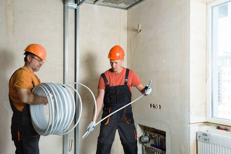 Workers are installing a pipe for the warm floor in the apartment. They are unwinding tube. Stock Photo