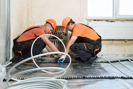 Workers are installing a pipe for the warm floor in the apartment. They are unwinding tube.
