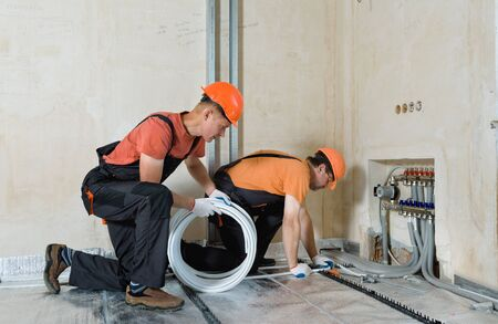 Workers are installing a pipe for the warm floor in the apartment. They are a bend pipe.