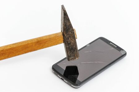 The hammer is smashing the screen of a smartphone. There are cracks in the glass.
