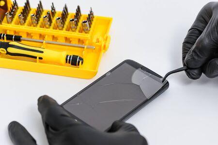an is removing broken glass for smartphone with tweezers.