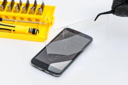 Man is removing broken glass for smartphone with tweezers.