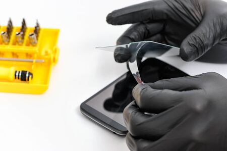 Human hands are removing a film from the protective glass of the screen of a smartphone.