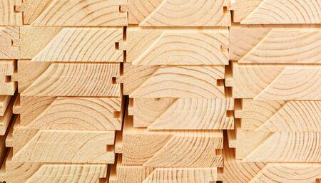 Widok od końca ułożonych w stos desek podłogowych. Zbliżenie konstrukcji drewnianej.