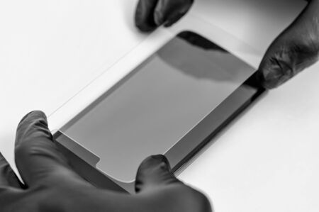 A man is installing a protective glass on the screen of a smartphone. Banco de Imagens