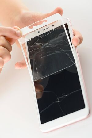 The human hand is removing broken glass from a smartphone screen.
