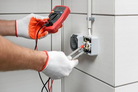 An electrician is using a multimeter to measure the voltage in a wall outlet. 写真素材