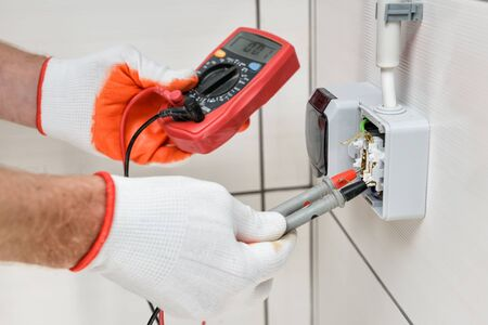An electrician is using a multimeter to measure the voltage in a wall outlet. Imagens