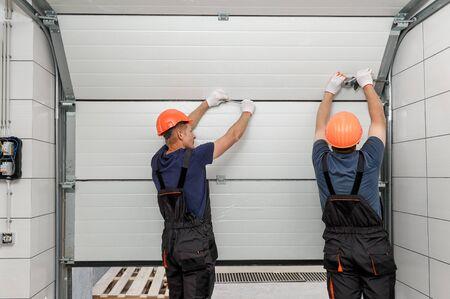 Gli operai stanno installando i cancelli di sollevamento del garage.
