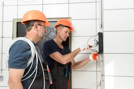 Electricians are installing out wall wiring. They are connecting wires in the junction box. Stockfoto - 132314779