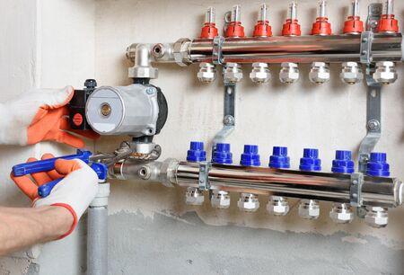 A plumber is fixing a water pump in a floor heating system.