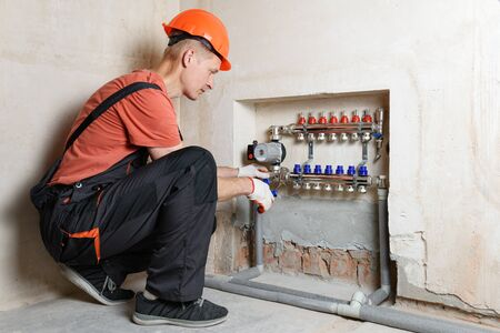 The plumber is fixing the distribution manifold to the floor heating system.