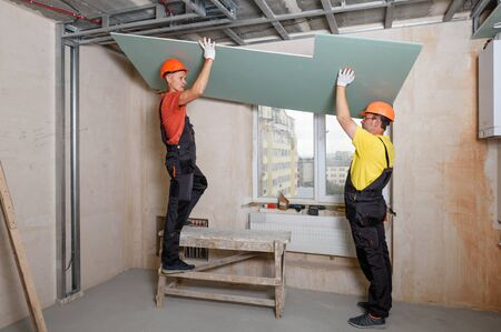 Workers are lifting plasterboard for further attaching to the ceiling. Stock fotó