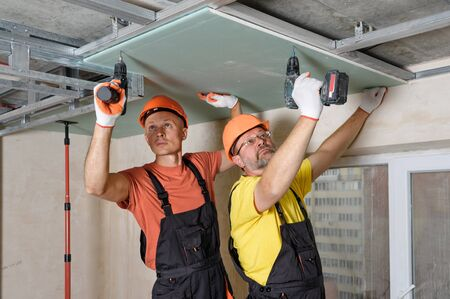 Workers are using screwdrivers to mounting plasterboard to the ceiling. Stock fotó
