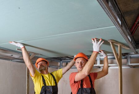 Installation of drywall. Workers are mounting a plasterboard to the ceiling. Stock fotó