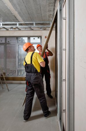 Drywall installation. Workers are mounting a plasterboard to the wall.  Stock fotó