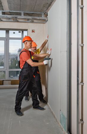 Workers are using screwdriver to attach plasterboard to the wall. Stock fotó