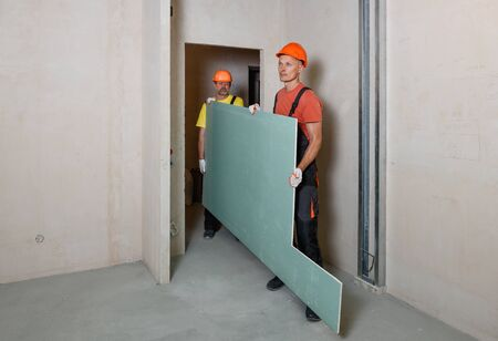 Workers are carrying plasterboard for further attachment to the ceiling. Imagens
