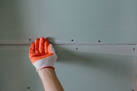 A worker is attaching the mesh to the seams between the plasterboards.