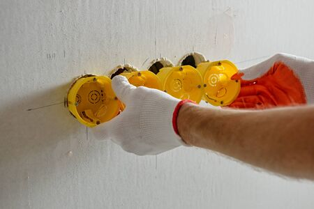 A worker is installing a group of socket boxes into drywall. Imagens