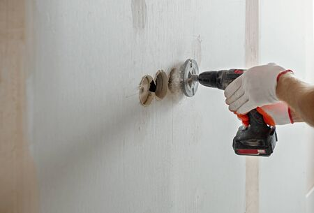 A worker is making holes in the drywall to install the outlet in the future. Imagens