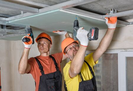Workers are using screwdrivers to installing plasterboard to the ceiling. Imagens