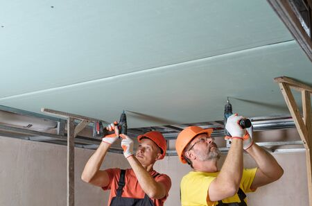 Workers are using screwdrivers to attach plasterboard to the ceiling. Imagens
