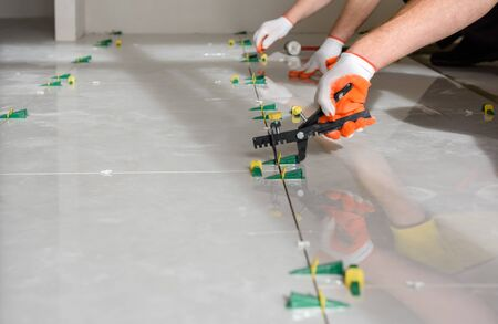 Workers are using plastic clamps and wedges to leveling the large ceramic tile on the floor.