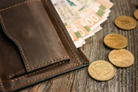 Brown leather wallet with banknotes and coins on old wooden surface. Close up. Imagens