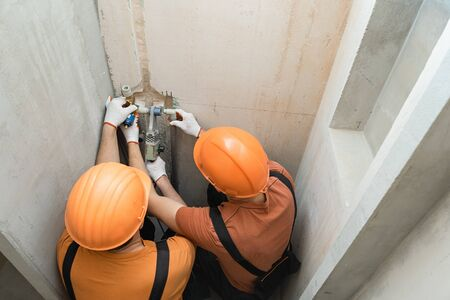 Workers are soldering a wall faucet for a built-in shower.