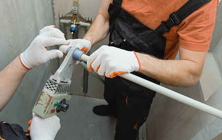 Workers are soldering wall pipes for a built-in shower.