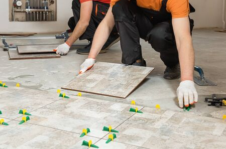 Two workers are installing ceramic tiles on the floor. Stockfoto