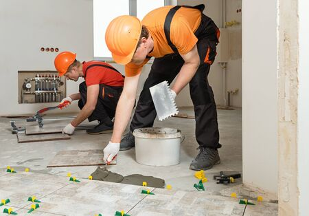 Two workers are installing ceramic tiles on the floor. Banque d'images